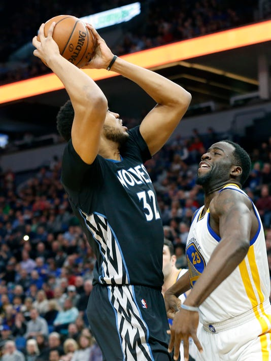 Minnesota Timberwolves' Karl-Anthony Towns, left, looks to shoot as Golden State Warriors' Draymond Green defends during the first half of an NBA basketball game Friday, March 10, 2017, in Minneapolis. (AP Photo/Jim Mone)