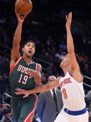 Milwaukee Bucks guard Jerryd Bayless (19) passes over New York Knicks guard Pablo Prigioni (9) in the second half of their preseason NBA basketball game at Madison Square Garden, Monday, Oct. 20, 2014, in New York.