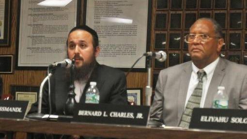 Yehuda Weissmandl, president of the East Ramapo School Board (left,) speaks at a school board meeting at district head quarters in Spring Valley. (Right) Trustee Bernard Charles.