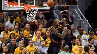 Cleveland Cavaliers forward LeBron James (23) attempts a layup in front of forward Larry Nance Jr. (22) and Boston Celtics forward Al Horford (42) during the first half of game three of the Eastern conference finals in the 2018 NBA Playoffs at Quicken Loans Arena.