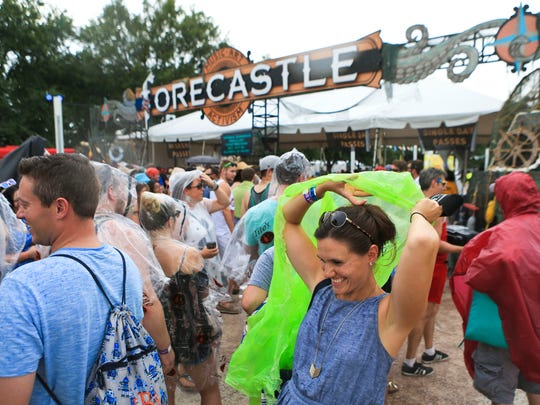 Rose Ann Byers puts on a rain slicker while waiting outside the west entrance of Forecastle Festival Friday after the festival was evacuated due to bad weather.