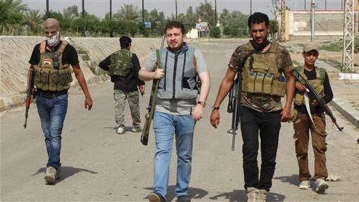 In this Sunday, May 10, 2015 photo, Sunni tribal fighters secure central Ramadi, the capital of Anbar province, 115 kilometers (70 miles) west of Baghdad, Iraq. Iraqi authorities on Friday signed up the first batch of 1,000 recruits for a new Sunni militia to help its security forces take back the western Anbar province from the Islamic State group, after years of reluctance to arm and train the tribal fighters. (AP Photo)