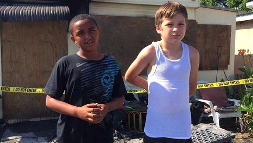 Isiah Francis, 10, left, and Jeremiah Grimes, 11, explain how they ran into a burning trailer at Lake John's Motel Efficiency on West Colonial Drive in Oakland, Fla., late Tuesday morning and saved two young children on June 16, 2015. (Tiffany Walden/Orlando Sentinel via AP) MAGS OUT; NO SALES