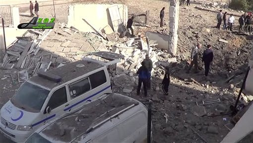 This image taken from video provided by the Syrian activist-based media group Azaz Media Center, which has-been verified and is consistent with other AP reporting, shows people gathered around destroyed vehicles in Azaz, Syria Syria on Monday. Turkey says Kurdish forces have been expelled from areas around the northern Syrian town of Azaz after a weekend of cross-border shelling.
