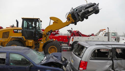 Mangled vehicles rest on the northbound Interstate 95 shoulder at the Washington Boulevard exit after a series of crashes that shut down I-95 in Baltimore, Md., on Saturday, Dec. 17, 2016. An ice storm created slick conditions, sparking a chain reaction pile-up involving dozens of vehicles. (Karl Merton Ferron/The Baltimore Sun via AP)