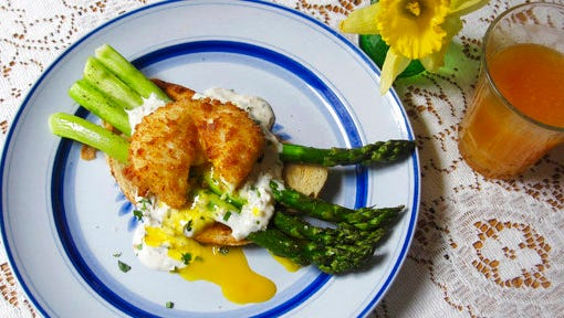 This April 2017 photo shows roasted asparagus toast with a fried poached egg in New York. The base is artisanal toast brushed with olive oil and topped with roasted asparagus. The asparagus can be prepped and pre-roasted and then warmed in the oven before serving.