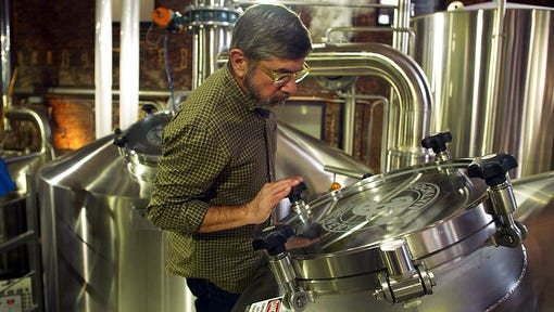 In this Feb. 24, 2017, image from video, Brooklyn Brewery co-founder Steve Hindy inspects brewing equipment inside the brewery, in New York. Brooklyn Brewery is now one of the country's biggest craft breweries, but Hindy remembers when he had to convince a small Brooklyn club to carry his beer.
