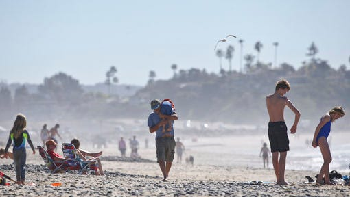 FILE - In this Feb. 16, 2016 file photo, a man carries a young boy over his shoulder as he walks among beach goers enjoying unusually warm winter temperatures in Encinitas, Calif. Global warming's milder winters will likely nudge Americans off the couch more in the future, a rare, small benefit of climate change, a new study finds.