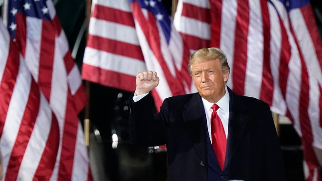 President Donald Trump pumps his fist before speaking at a campaign rally, Monday, Sept. 21, 2020, in Swanton, Ohio.