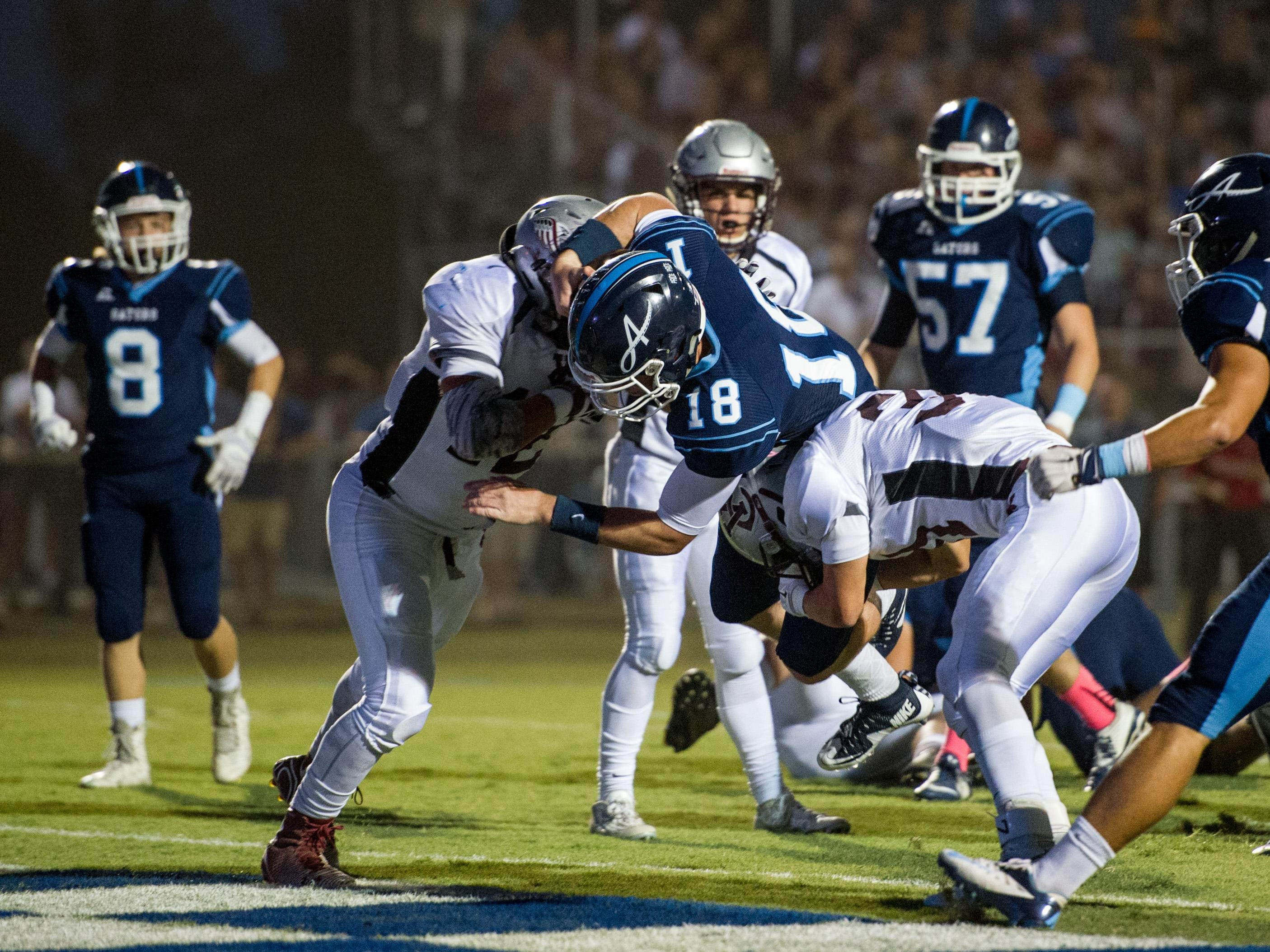 Ascension Episcopal quarterback Jake Arceneaux (18) dives into the end zone to score a touchdown during the first half.