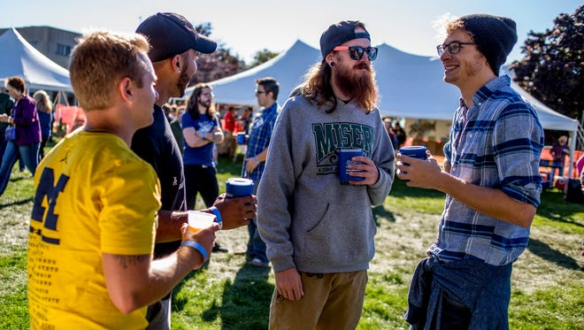 Jon Dankenbring, right, Brandon Howcroft, Davon Hawkins, and Leon Boyd-Cleaver, all of Port Huron, talk and drink beer together during the Port Huron Beer Festival Saturday, Sept. 24, 2016, at Kiefer Park in Port Huron.
