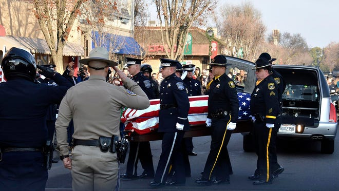 Law enforcement officials carry the casket of Newman Police Cpl. Ronil Singh into the Westside Theatre for a public viewing in Newman, Calif., Friday, Jan. 4, 2019.Prosecutors on Wednesday, Jan. 2, charged Gustavo Perez Arriaga in Singh's killing. Perez Arriaga, who was in the country illegally, was arrested after a dayslong manhunt as he prepared to flee to Mexico, authorities said. (Deke Farrow/The Modesto Bee via AP)