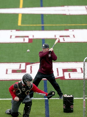 South Kitsap baseball coach Marcus Logue takes a swing from the end zone of the school's football stadium in the rain this past week. The Wolves' grass baseball field has been unplayable most of the season.