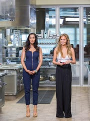 """Padma Lakshmi and Chrissy Teigen stand inside the La Quinta High School Culinary Arts kitchen during the """"Top Chef"""" episode titled """"Big Gay Wedding."""""""