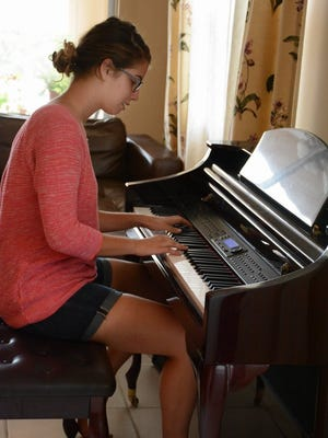 Naples resident and FGCU student Maryssa Pallis plays piano in her home. Maryssa wants to feed the world, using sustainable micro-agriculture. Lance Shearer/Citizen Correspondent