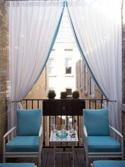 The turquoise cushions on the covered deck are paired with neutral curtains which help to define the space.