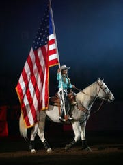 Patrick Dove/Standard-Times San Angelo Stock Show & Rodeo Ambassador Caylee Hardin carries the American flag into the arena Saturday afternoon during the opening ceremony of the sixth performance of the 84th annual San Angelo Stock Show & Rodeo at Foster Communications Coliseum.