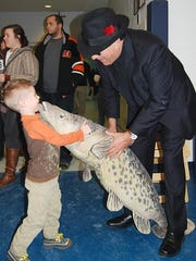 """Alister Roland, of Burlington, gives the stuffed cod a hug as """"Codfather of Sole"""" John Geisen, of Florence, greets attendees at Mary Queen of Heaven School Fish Fry in Erlanger."""