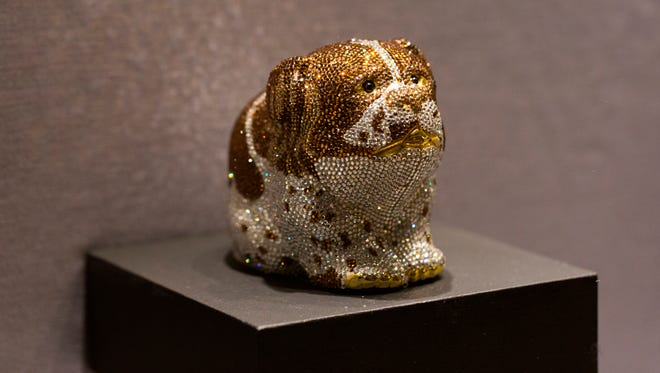 """This undated photo provided by the Museum of Arts and Design shows a brown and white """"Millie"""" minaudière with rhinestones owned by Barbara Bush and based on the Bush family dog. It is part of the exhibit """"Judith Leiber: Crafting a New York Story."""" (Jenna Bascom/Museum of Arts and Design via AP)"""