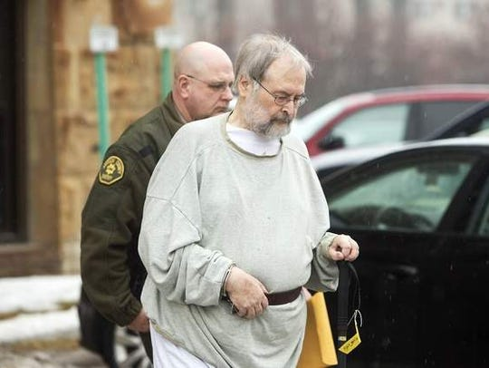 John Bloomfield is escorted from the Johnson County