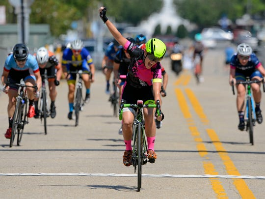 Heather Nelson celebrates after crossing the finish line first during the Women's race of the Subway Pensacola Cycling Classic Sunday, September 17, 2017 in downtown Pensacola.
