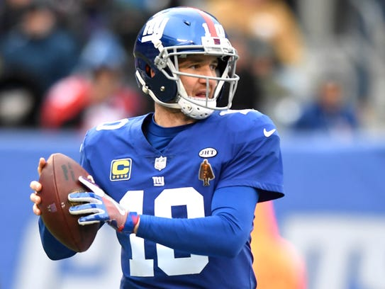New York Giants quarterback Eli Manning (10) faces