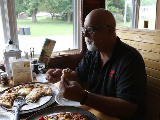Robert Schaalma, owner of Rob's Redwood restaurant in Unity, enjoys a slice of his signature pizza at the restaurant July 27, 2016. Shaalma uses more than a pound of cheese on his homemade pizzas.