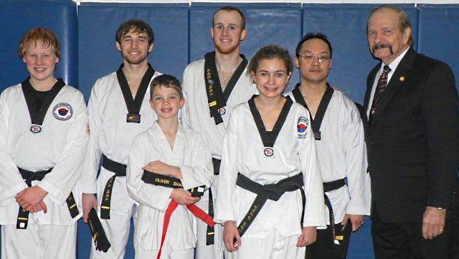 Master instructor Dwight Stevens, right, poses with black belt students Daniel Roach, Jacob Kujawa, Oliver Shave, Tanner Rogers, Anika Brandl and Chong Chang.