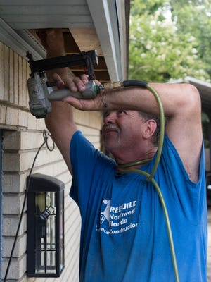 Scott Dunbar a contractor for Rebuild Northwest Florida works to completes a retrofit to the home by adding tress ties and closing off the soffit Friday afternoon June 30, 2017.