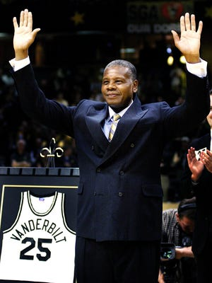 Perry Wallace, the first black player in the SEC, waves to the cheering fans during a ceremony to retire his No. 25 Vanderbilt jersey on Feb. 22, 2004.