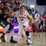 Brandon Bos of the University of South Dakota dribbles past Kory Brown on North Dakota State on Jan. 30 at the DakotaDome. The men's basketball schedule released for the 2014-15 season has the Coyotes playing five teams that reached the NCAA Tournament last year.