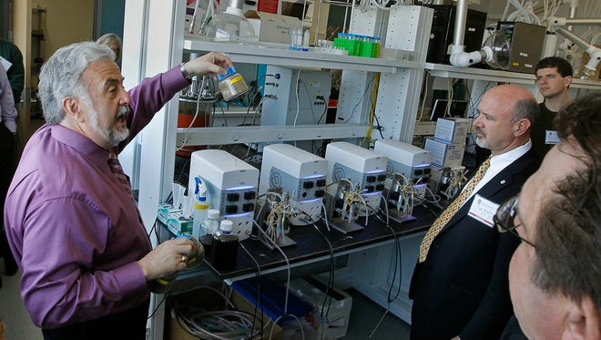 Tim Donohue (left), director of the Great Lakes Bioenergy Research Center at UW Madison's Wisconsin Energy Institute building,  shows visitors the lab where they are studying alternative clean fuels such as corn and switchgrass as sources for clean energy during a tour in 2014.