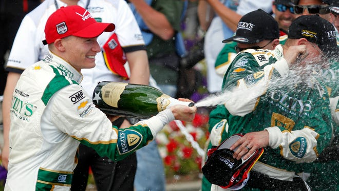 Mike Conway, left, of England sprays his team with champagne in celebration of winning the IndyCar Grand Prix of Long Beach race Sunday.