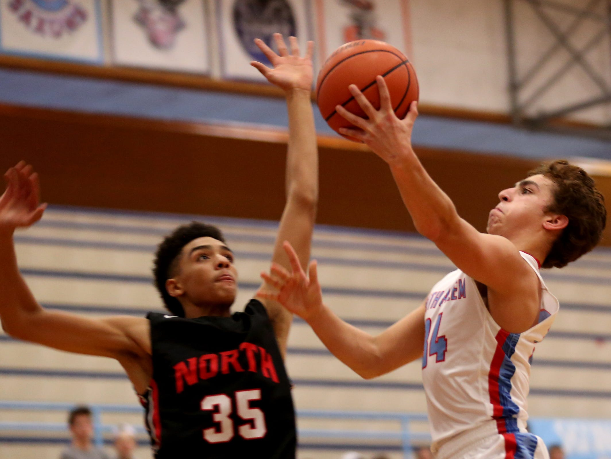South Salem's Gavin Baughman (34) goes for two points as North Salem's Jordan Sampson (35) tries to block his shot in the North Salem vs. South Salem boy's basketball game at South Salem High School on Tuesday, Feb. 16, 2016. South Salem won the game 82-36, clinching the Greater Valley Conference Championship.