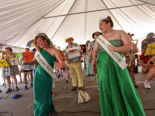 Asparagus Queen 2016 Mary Harris, left, of Hart and runner-up Mandy Achterhof of Walkerville dance as the Scottville Clown Band plays in the entertainment tent during the National Asparagus Festival in Hart, Mich., on June 11, 2016.