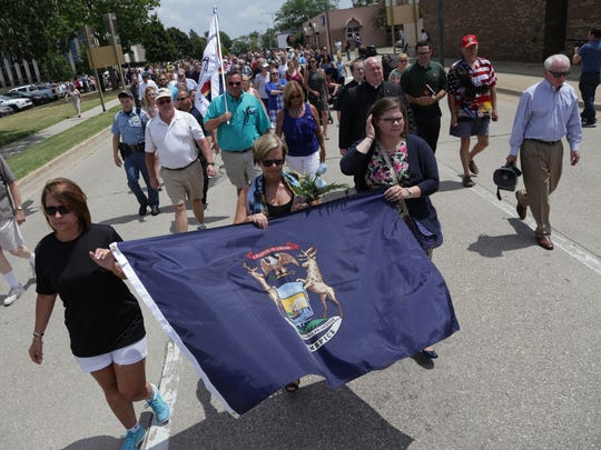 (Right to left) Elizabeth Peterson, Patricia Ceresa and Shelley Newman lead a group of hundreds of people while marching in memory of bailiffs Ron Kienzle and Joseph Zangaro from the Berrien County Courthouse in St. Joseph on Tuesday July 12, 2016, to the Berrien County Law Enforcement Memorial after the bailiffs were shot and killed by inmate Larry Gordon on Monday at the courthouse.