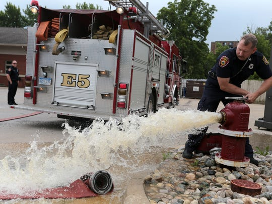 Captain Dave Wylie of the Wayne Fire Station 5 opens a fire hydrant behind the station as he prepares to hook up the hose to conduct a training exercise, on Thursday, June 23, 2016.