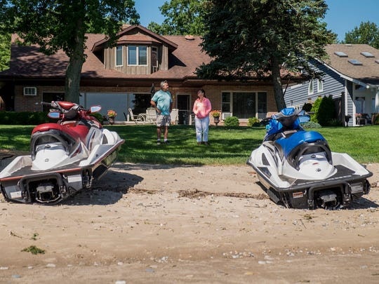 Randy Nabozny, left, and Diane Sparling look at damaged boats on a beach on Lake Huron in Burtchville Township. The boats were damaged and pulled onto the beach after a strong north wind blew through Monday afternoon.