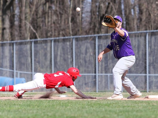 St. Johns' Chad Gilroy dives back into first base while