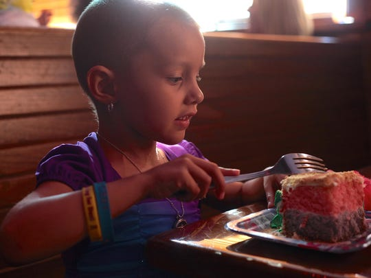 Desi Cechin, 6, takes a bite of her cake during her Make-A-Wish presentation Monday at Outback Steakhouse in Palm Desert.