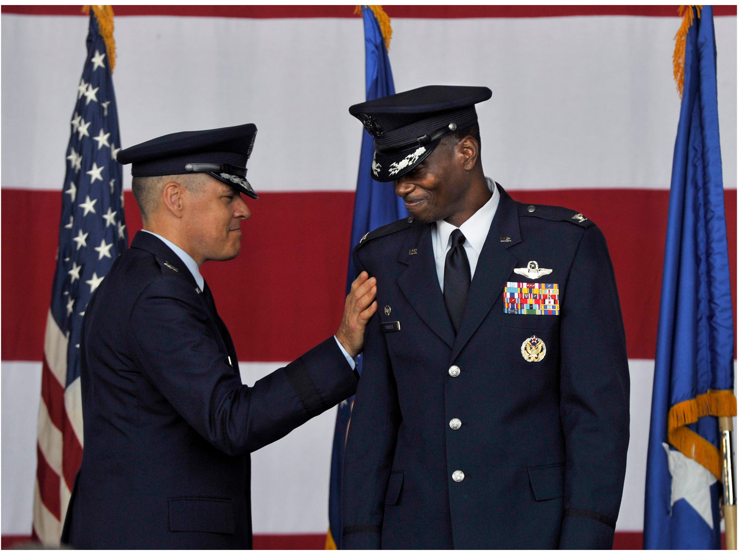 Eighth Air Force commander Major Gen. Thomas Bussiere pats Col. Brandon Parker on the shoulder after officially naming Parker as 7th Bomb Wing commander Aug. 4 at Dyess Air Force Base. Parker, the first African-American Dyess commander, assumed command of the base from Col. David Benson in a change of command ceremony.