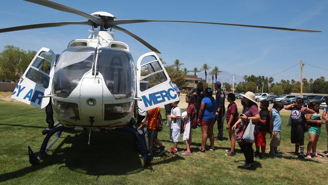 5th graders from Dr. Carreon Academy climb in and out of a air ambulance helicopter during a disaster drill at JFK Memorial Hospital in Indio on Friday. The drill gave the students a look at the different career in emergency services.