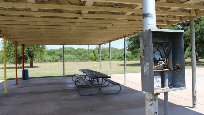 An electrical box is without a cover at the Kirby Park pavilion. A nearby water fountain does not work, and the structure, while having brightly colored poles on the north side, is in need of a paint job.