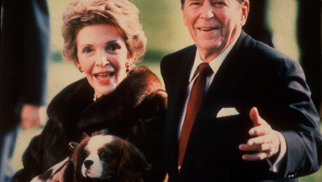 "FILE - This December 1986, file photo shows first lady Nancy Reagan holding the Reagans' pet Rex, a King Charles spaniel, as she and President Reagan walk on the White House South lawn. The former first lady was buried beside her ""Ronnie"" March 11, at the library they loved, after being mourned and celebrated by family and hundreds of friends from Hollywood, Washington and beyond in a private service. Mrs. Reagan, who died March 6 at 94, planned the smallest details of her funeral. (AP Photo/Dennis Cook, File)"