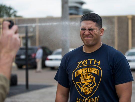 Police cadet Richard Reyes III is sprayed in the face