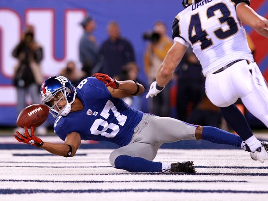 EAST RUTHERFORD, NJ - SEPTEMBER 19:  Domenik Hixon #87 of the New York Giants catches a 22-yard touchdown reception in the second quarter against Craig Dahl #43 of the St. Louis Rams at MetLife Stadium on September 19, 2011 in East Rutherford, New Jersey.  (Photo by Nick Laham/Getty Images)