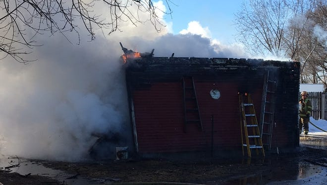 A shed burns Thursday morning at 2648-10th St. NE in Sauk Rapids. Firefighters are trying to determine whether a wood-burning stove inside the shed might have been the cause.