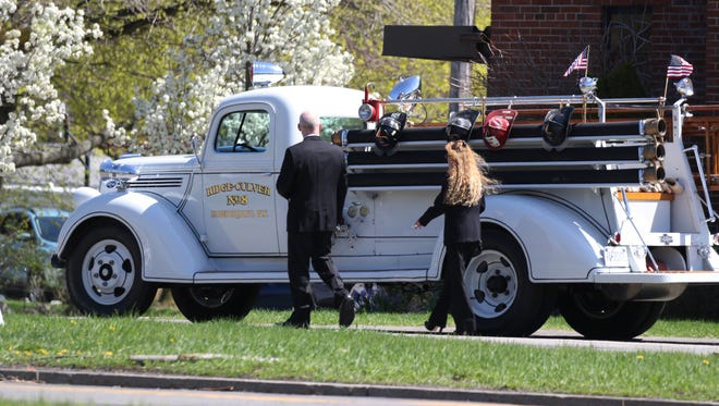 A couple that left the memorial Mass at St. Kateri at St. Cecilia Church for William Aman walk by one of the older firetrucks he had driven as a member of the Ridge Culver Fire Department. He was a 72-year member, past fire chief and a 20-year fire commissioner with the district.
