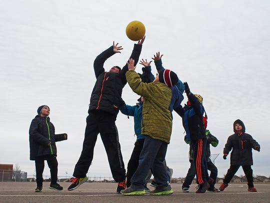 A group of first-graders play a kickball game during