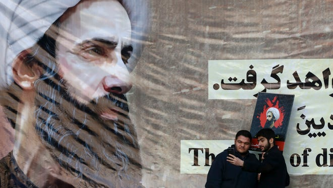 Iranian men take a selfie with a poster of Sheikh Nimr al-Nimr, a prominent opposition Saudi Shiite cleric who was executed Saturday by Saudi Arabia. The executions inflamed Sunni-Shiite tensions between Saudi Arabia and Iran.